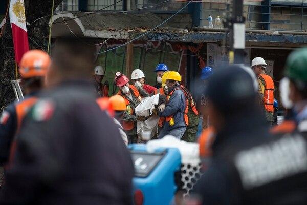 Rescatistas trasladaban el cuerpo de una persona que hallaron entre las ruinas de un edificio que se desplomó en Ciudad Jardín, un barrio de la capital mexicana.