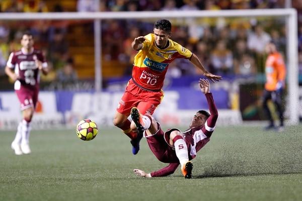El defensor de Herediano José Mena disputa el balón con el mediocampista de Saprissa Ulises Segura, el pasado miércoles en el estadio Eladio Rosabal Cordero.   JOSÉ CORDERO