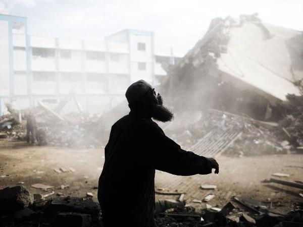 Un hombre ayuda hoy a limpiar los escombros del edificio del Ministerio de Interior, derribado por los ataques isaelíes.   AFP.