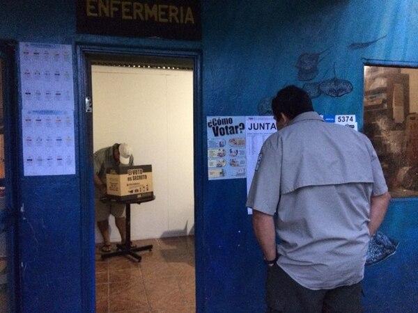 Momentos en que el guardaparques Keylor Morales observa la lista de diputados y otro vota a lo interno de la enfermería de la Isla del Coco.