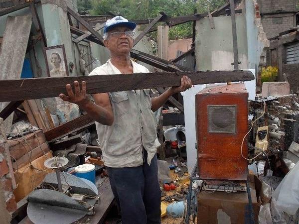 Un cubano intenta recuperar algo de lo quedó de su casa, demolida por los vientos del huracán Sandy, en la ciudad oriental de Santiago. | AFP