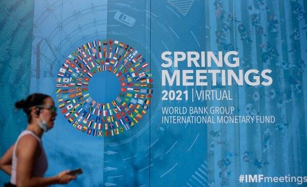 Una corredora pasa junto a la sede del Fondo Monetario Internacional (FMI) en Washington, DC, el 5 de abril del 2021. Las vacunas aceleradas y una avalancha de gastos gubernamentales, especialmente en los Estados Unidos, han impulsado las perspectivas para la economía mundial, pero se debe hacer más para evitar cicatrices permanentes, dijo el FMI este 6 de abril. Foto: AFP.