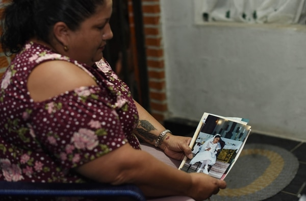 Rosmery Cordero sostiene en sus manos uno de los momentos que atesora con más cariño de su hija Karolay: la primera comunión. Foto: Carlos Gonzalez / Agencia Ojo por ojo