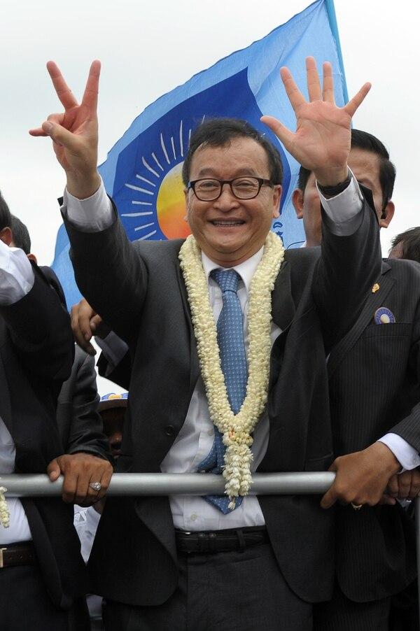 El líder de la oposición del Partido Rescate Nacional de Camboya (CNRP) Sam Rainsy (centro ) saluda a sus partidarios este viernes en Camboya.