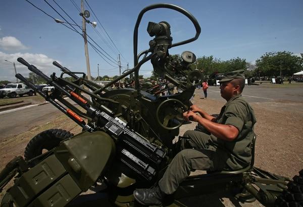 Un soldado usó una ametralladora en una exposición en Managua.   EFE