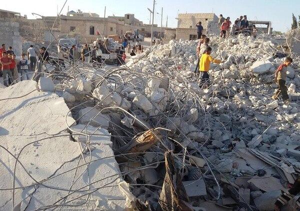 Habitantes de Kfar Derian, Siria, observan los escombros de un edificio alcanzado por un bombardeo de la coalición. Kfar Derian es un bastión del grupo yihadista Frente al-Nusra. | AP