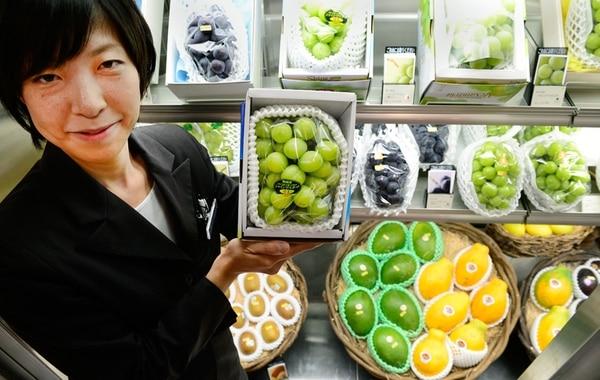 Miyuki Kaida muestra un paquete de uvas perfectas en el mercado donde trabaja, en Tokio.   AFP.