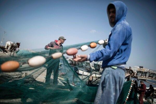 Pescadores palestinos cargan sus redes dentro de un bote antes de salir a pescar en aguas del Mediterráneo, en la ciudad de Gaza. Israel suavizó las restricciones y ahora les permite navegar hasta a nueve millas naúticas de la costa.