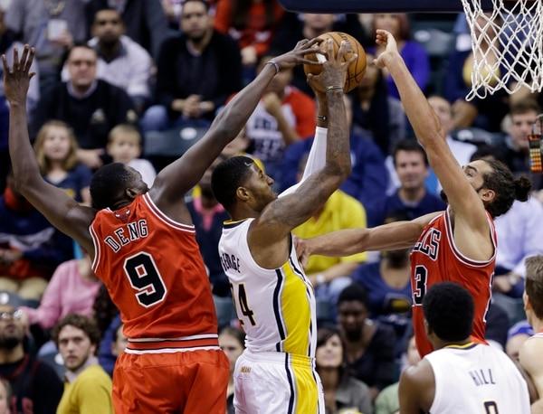 Paul George (centro) intenta anotar ante la marca de los jugadores de los Bulls Luol Deng y Joakim Noah.