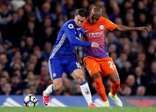 El belga Eden Hazard cubre la pelota ante la marca del volante del Manchester City Fernandinho