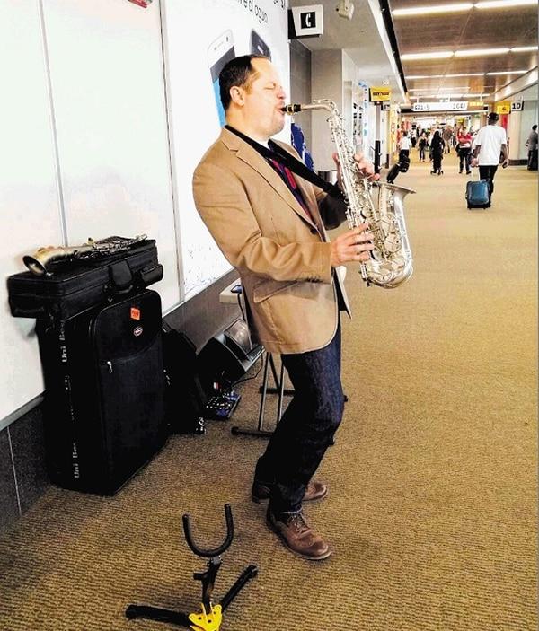 En las instalaciones del Aeropuerto Juan Santamaría, donde toca el sax de lunes a domingo, de las 8:30 a. m. a pasado el mediodía).
