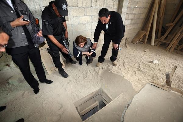 La fiscala general de México, Arely Gómez, y otras autoridades observaban el domingo la desembocadura del túnel en una vivienda cercana al penal de El Altiplano (derecha). | AFP Y AP