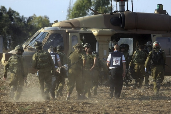 Soldados israelíes trasladan a un compañero herido por metralla de mortero que explotó dejando cuatro muertos en el sur de Israel en la frontera con la Franja de Gaza.