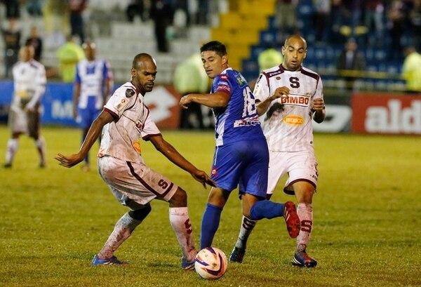 Los zagueros Adolfo Machado (izq.) y Alexander Robinson intentan detener al brumoso Carlos Hernández, en la derrota del domingo. | CARLOS BORBÓN
