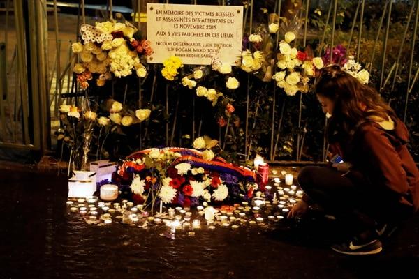 Una mujer observó ayer las flores y las velas expuestas bajo una placa conmemorativa en memoria de las víctimas de los ataques que se llevaron a cabo el 13 de noviembre del 2015 en la capital francesa.