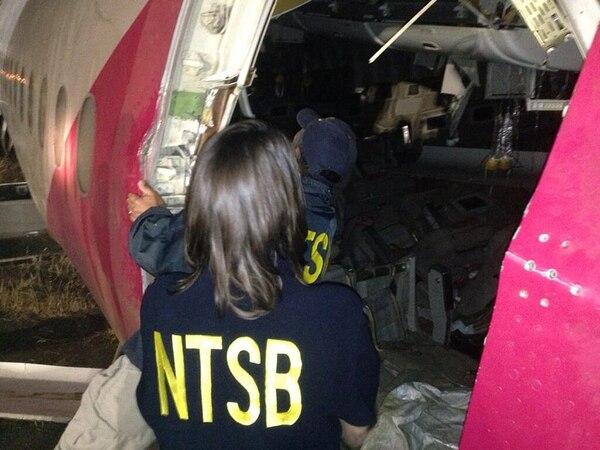 Investigadores de la NTSB inspeccionan el fuselaje dañado del avión de Asiana Airlines.
