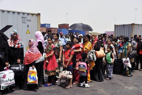 Personas de origen indio esperaban turno ayer para abordar un barco en el puerto de Hodeidah, Yemen. Millares de extranjeros residentes en el país árabe están saliendo en vista del agravamiento del conflicto político-militar que enfrenta a los insurgentes hutíes con milicias rivales y una coalición árabe.   EFE