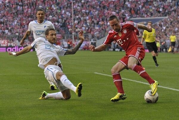 El defensor del Hoffenheim, Fabian Johnson, se barre en su intento por frenar el avance del ariete francés Franck Ribery, del Bayern Múnich.   AFP