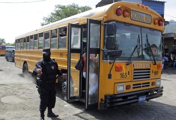 Agentes de la Policía Nacional Civil (PNC) de El Salvador montan guardia en una de las principales terminales de autobuses en San Salvador