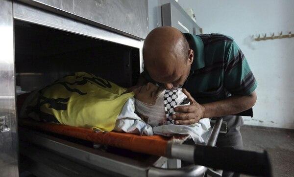 Un familiar del joven palestino Yousef Abú Zagha le besa la cara durante los preparativos para el funeral en el campo de refugiados de Jenín, Cisjordania. El menor murió de un balazo en las redadas del Ejército israelí.   EFE