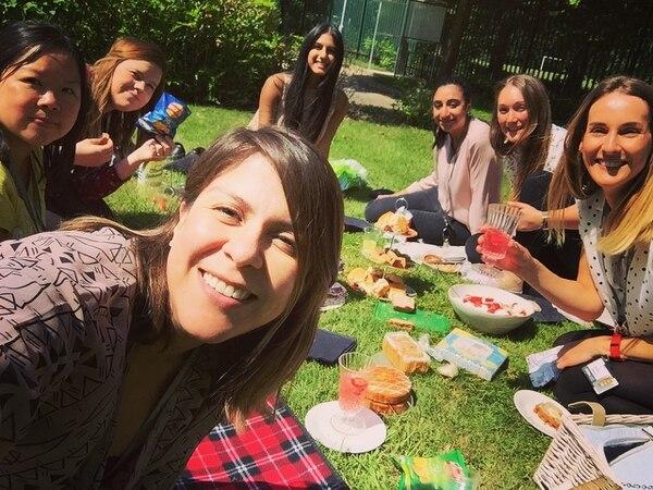 La tica Diana Valerio López (al frente) con compañeras de trabajo, quienes aprovechan un día soleado para comer al aire libre.