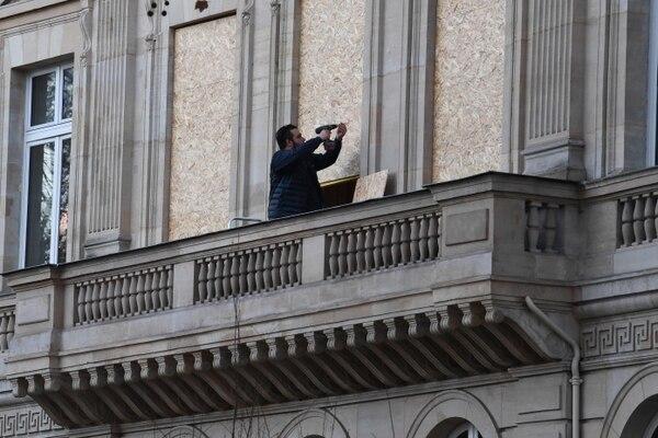 Un hombre colocaba una lámina de madera para protegerlos ventanales de su apartamento, en París, en la víspera de las protestas programadas para este sábado 8 de diciembre del 2018.