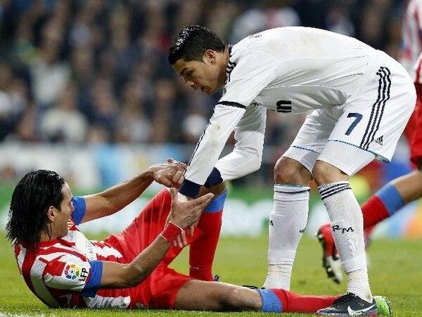 El portugués Cristiano Ronaldo ayuda al colombiano Radamel Falcao a reintegrarse al juego tras un fuerte golpe que el colchonero recibió. El duelo de titanes, sin duda, lo ganó el merengue, pues aportó gol y asistencia.   EFE