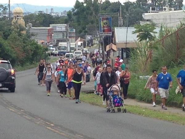 Decenas de romeros caminan sobre la vía que conduce a La Galera en Curridabat esta mañana.