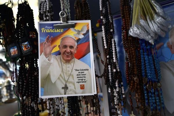 Carteles con imágenes del papa Francisco y rosarios en un puesto de venta en Cali, Colombia.