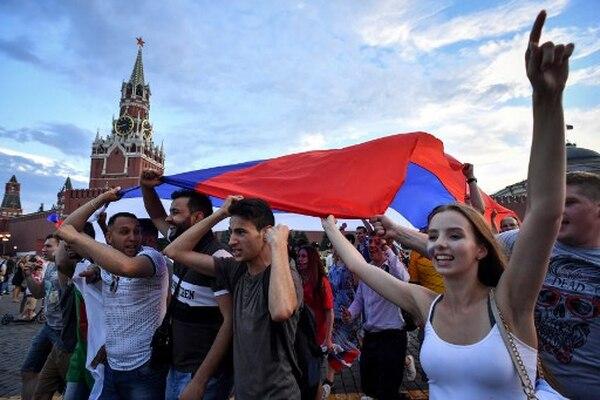 Ondeando la bandera. Estos jóvenes celebran la victoria de Rusia sobre España en la histórica Plaza Roja de Moscú. / AFP PHOTO / Yuri KADOBNOV