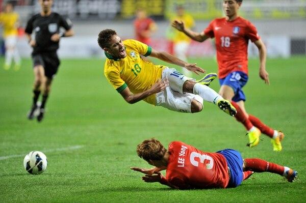 Neymar (amarillo) detenido sin contemplaciones por la barrida del defensor coreano Lee Yong, durante el amistoso que ganó Brasil 0-2 en Seúl. | AFP