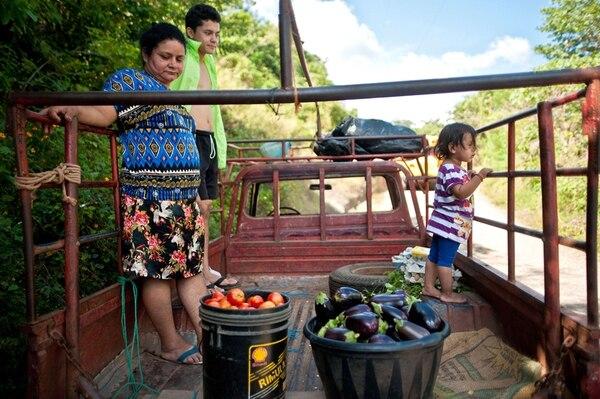 """Norma Elizabeth y su familia transportan cultivos que produjeron dentro del programa """"Canasta campesina"""".   AFP."""