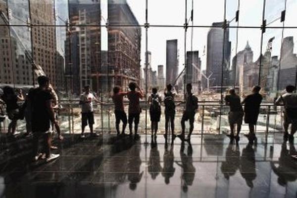 Turistas miran el sitio donde estuvieron las torres del World Trade Center en Nueva York, donde ya se empiezan a erguir nuevas construcciones. | THE NEW YORK TIMES