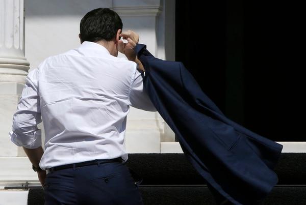 El primer ministro de Grecia, Alexis Tsipras, ingresaba el lunes a su despacho en Atenas, después de llegar de Bruselas, donde participó en la cumbre del Eurgrupo. | AP