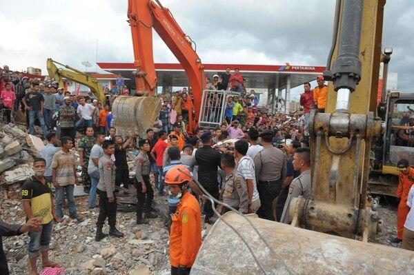 Miembros de un equpo de búsqueda y rescate junto con residentes rescatan a un sobreviviente del terremoto en Pidie Jaya, en la provincia indonesia de Aceh.