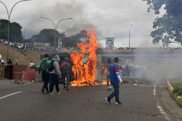 Los manifestantes venezolanos incendiaron una furgoneta durante una protesta contra el gobierno del presidente Nicolás Maduro, en el aniversario del levantamiento de 1958 que derrocó a la dictadura militar en Caracas, el 23 de enero del 2019. Foto: AFP