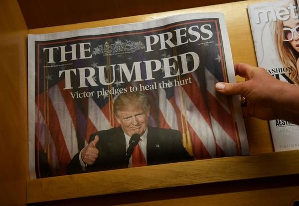 Una mujer toma un periódico local sobre el triunfo de Trump en Christchurch, Nueva Zelanda