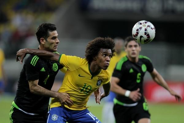 El brasileño Willian (derecha) disputa el balón con el defensor mexicano Rafael Márquez (izquierda) durante un partido amistoso previo a la Copa América.