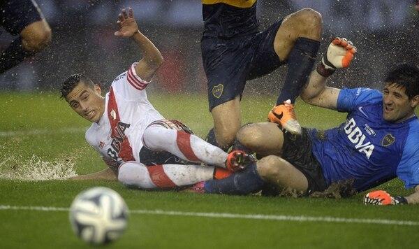 El defensor de River Plate, Funes Mori (izquierda), disputa el balón contra el guardameta xeneize Agustín Orión (derecha). El encuentró finalizó con empate a un gol. Mori no lo terminó pues salió expulsado.   AFP