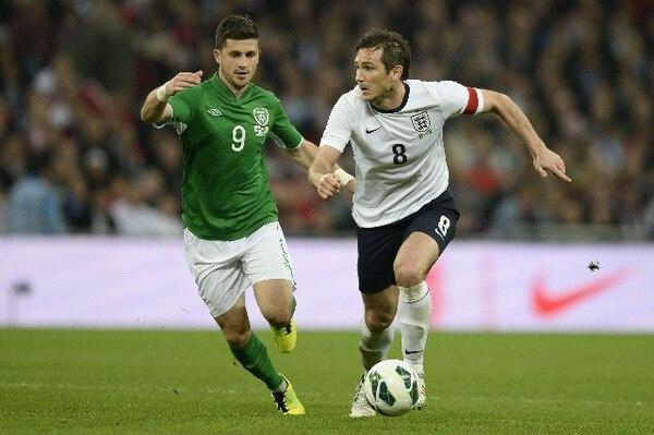 Shane Long, de Irlanda, marca a Frank Lampard, de Inglaterra.   AFP.