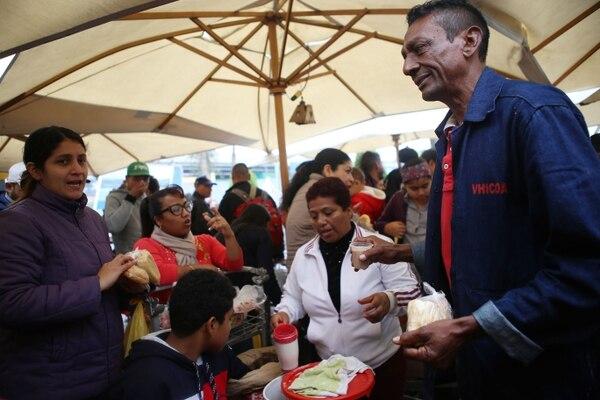 Los migrantes venezolanos reciben alimentos de los voluntarios a su llegada a la terminal de autobuses en el norte de Lima, después de viajar durante 20 horas desde Tumbes, al noroeste de Perú. Foto: AFP