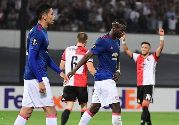 Los jugadores del Manchester United, Paul Pogba y Chris Smalling, evidencian la cara de derrota mientras jugadores del Feyernood celebran.