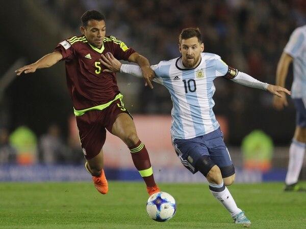 Lionel Messi disputa la pelota con Arquimedes Figuera de Venezuela