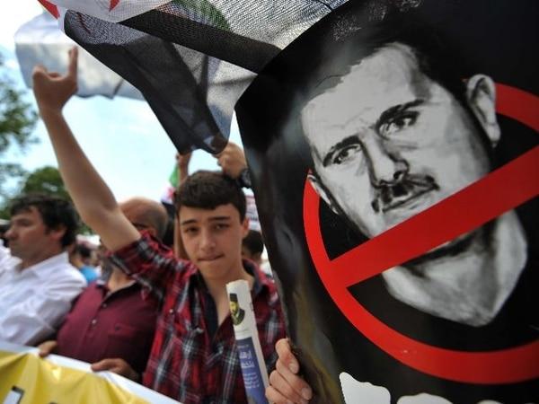 Turcos gritaron hoy consignas mientras otros sostenían una manta con la cara del presidente sirio Bashar al-Asad durante una protesta frente a la mezquita Fatih, en Estambul. Los principales opositores del régimen de Damasco empezaron ayer en Turquía una ronda de negociaciones de tres días. | AFP