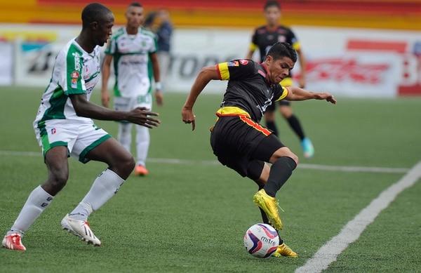 El volante Bryan Vega cubre la pelota ante la marca de Albin Bennett de Limón FC