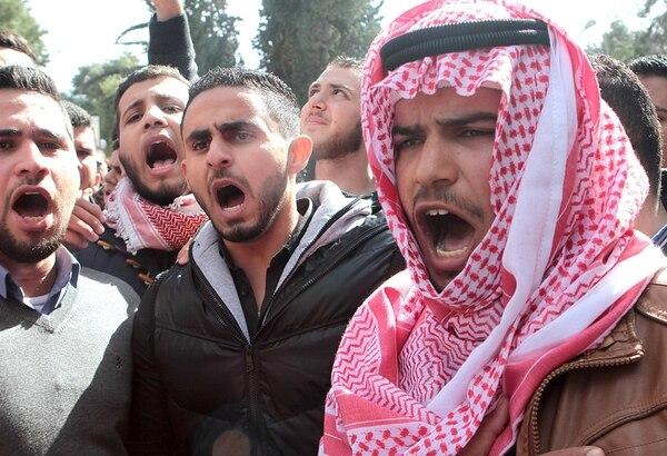 Estudiantes jordanos gritan consignas durante una manifestación en Amán para condenar el asesinato del piloto Muaz Kasasbeh, a quien el grupo ultrarradical quemó vivo después de su captura en diciembre anterior. | AFP