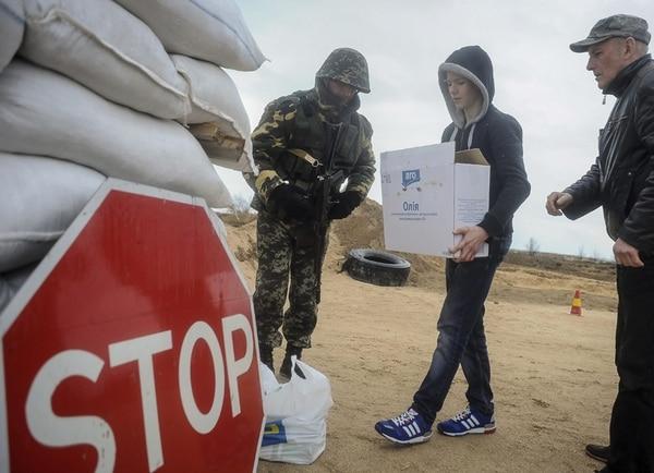 Varios ucranianos llevan alimentos a soldados de su país que montan guardia en un punto de control cercano a la frontera con la península Crimea, en el poblado de Strilkove. | EFE