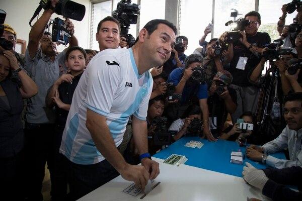 El candidato y excomediante Johnny Morales coloca su papeleta en la urna frente a las cámaras de la prensa vistiendo la camiseta de la selección guatemalteca.