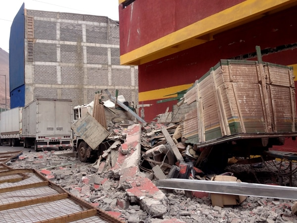 En la gráfica se muestra a un camión destruido en varias partes y un edificio dañado tras terremoto.