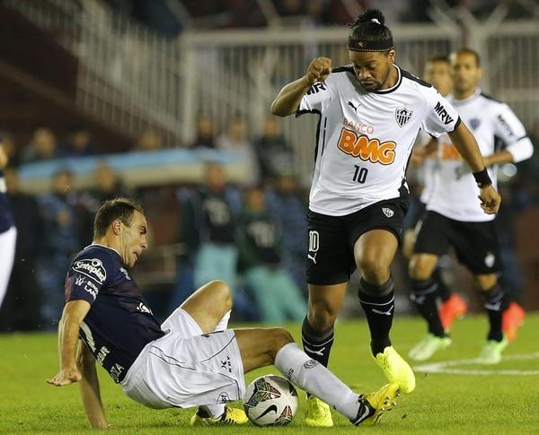 El jugador de Lanús de Argentina Leandro Somoza (izquierda) y de Atlético Mineiro de Brasil Ronaldinho disputan el balón este miércoles, durante el partido por la final de ida de la Recopa Sudamericana.